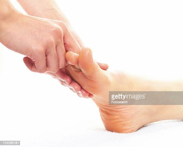 aesthetician who massages bottom of woman's foot, close up - estetista foto e immagini stock
