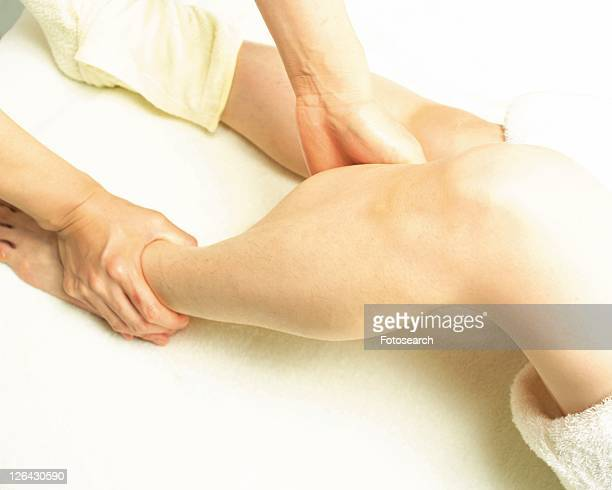 aesthetician who massages woman's foot, high angle view - estetista foto e immagini stock