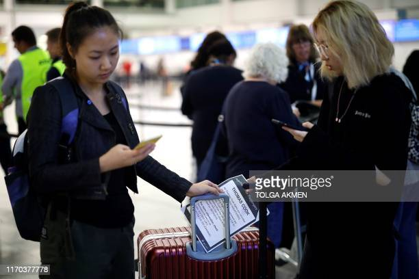 Affected passengers hold leaflets as they stand with their luggage after arriving at the closed Thomas Cook checkin desk at the South Terminal of...