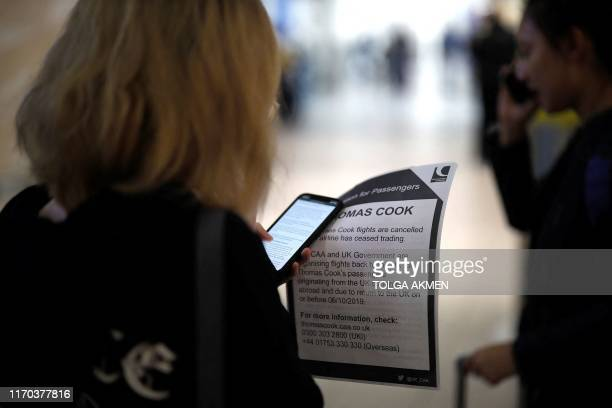 Affected passengers hold leaflets as they stand with their luggage after arriving at the closed Thomas Cook check-in desk at the South Terminal of...