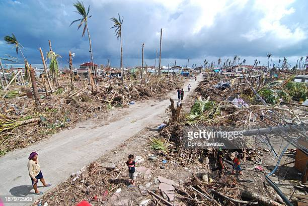 Affected residents survey the damage in Tacloban City on November 14 2013 in Tacloban Philippines Typhoon Haiyan which ripped through Philippines...