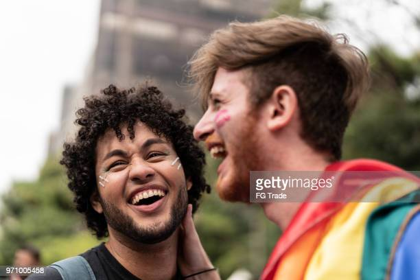 affection moment of gay couple in gay pride parade - pride stock pictures, royalty-free photos & images