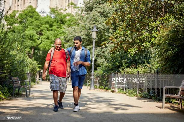 affectionate adult son walking with father in public park - approaching stock pictures, royalty-free photos & images