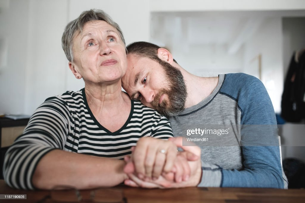Affectionate adult son with senior mother at home : Stock Photo