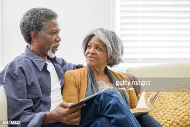 Affectionate African American couple on sofa with book and tablet