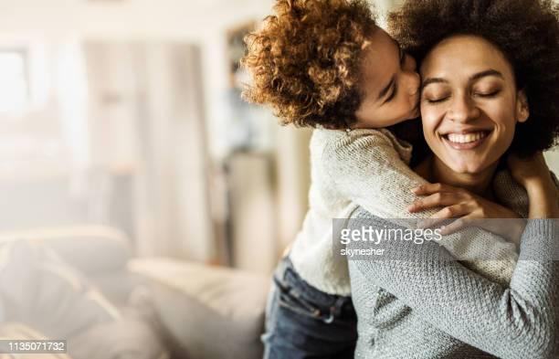 filha afectuosa do americano africano que beija sua matriz em casa. - mãe - fotografias e filmes do acervo