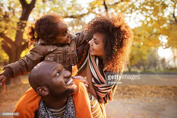 Affectionate African American family enjoying in autumn park.