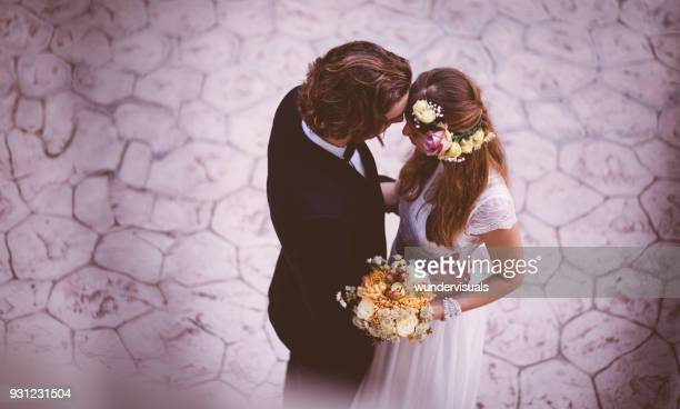 affectionate bride and groom embracing and dancing at wedding reception - marito foto e immagini stock