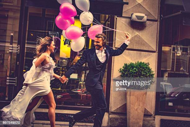 affectionate bride and groom, holding hands, happily run down the street - formalwear stock photos and pictures