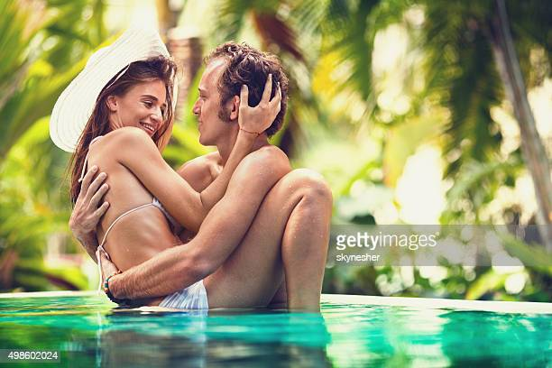Affectionate couple embracing in tropical pool.