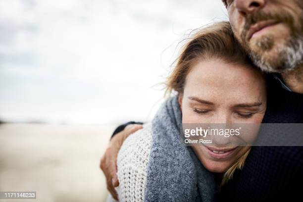 affectionate couple hugging on the beach - vertrauen stock-fotos und bilder