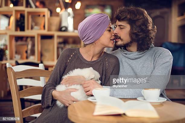 Affectueux couple embrassant dans un café.