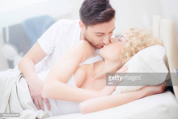 affectionate couple kissing in bed with white sheets - couple and kiss and bedroom stock photos and pictures