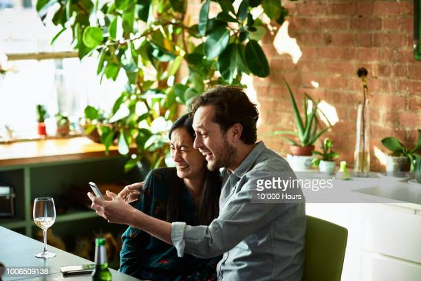 affectionate couple looking at smartphone and laughing - heterosexual couple stock pictures, royalty-free photos & images