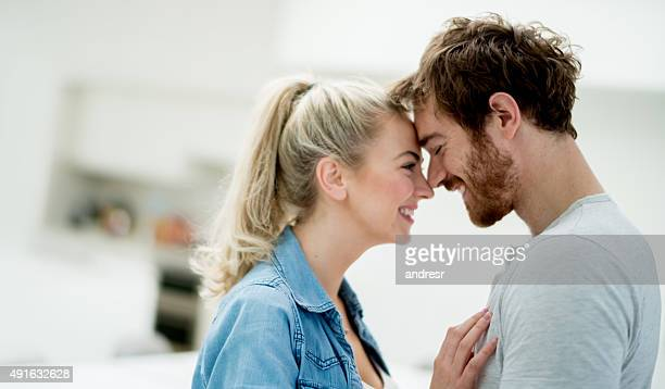 affectionate couple looking happy at home - angesicht zu angesicht stock-fotos und bilder