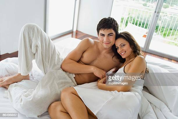 Affectionate couple lying in bed