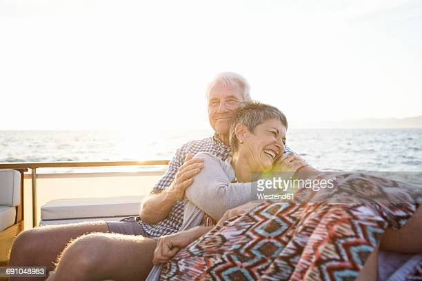 affectionate couple on a boat trip at sunset - ricchezza foto e immagini stock