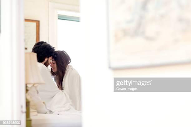 affectionate couple on bed at home - amanti letto foto e immagini stock