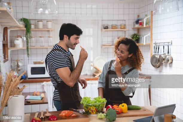 affectionate couple preparing salad - flirting stock pictures, royalty-free photos & images