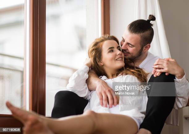 affectionate couple relaxing together at home - man touching womans leg stock photos and pictures