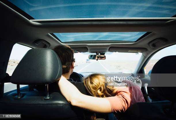 affectionate couple riding in sunny car - puerto del carmen stock pictures, royalty-free photos & images