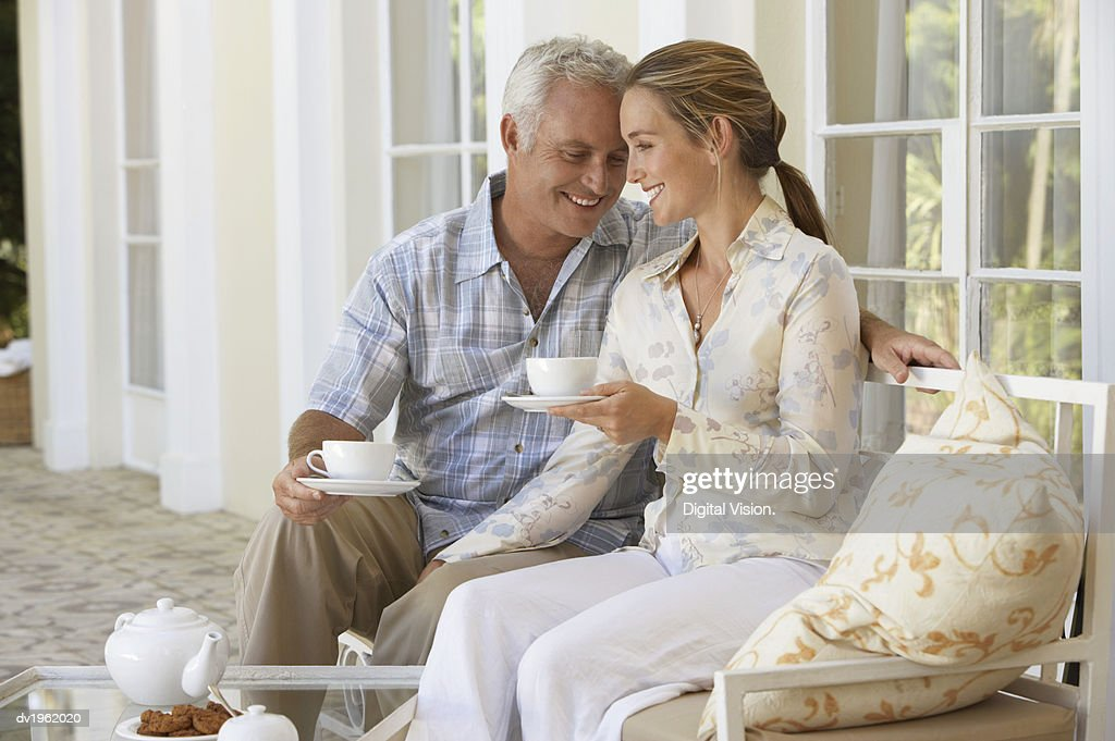 Affectionate Couple Sit on a Porch Holding Cups of Tea : Stock Photo