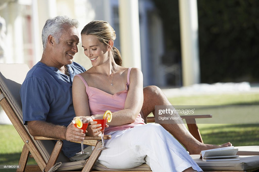 Affectionate Couple Sit on a Sun Lounger Holding Cocktail Glasses : Stock Photo