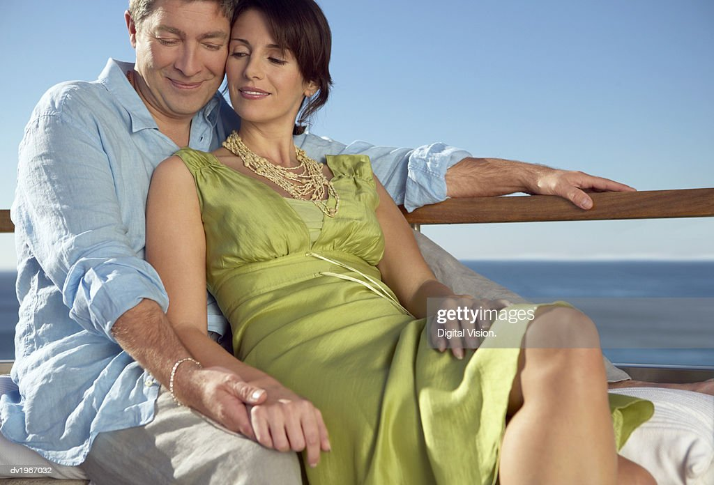 Affectionate Couple Sit Outdoors Holding Hands : Stock Photo