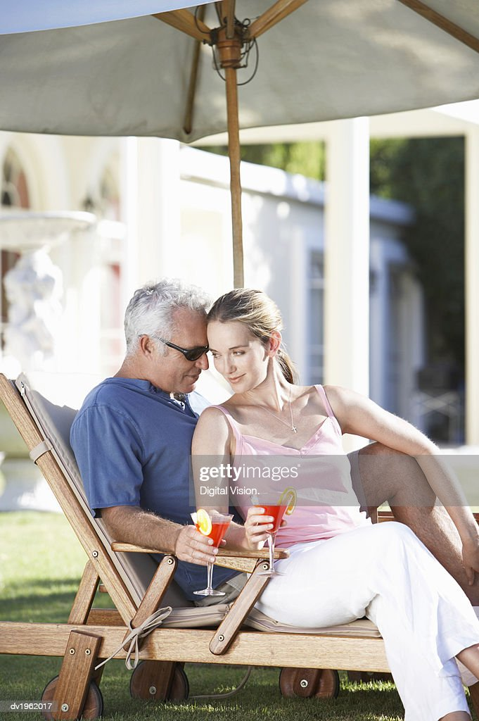 Affectionate Couple Sit Under a Parasol on a Sun Lounger Holding Cocktail Glasses : Stock Photo