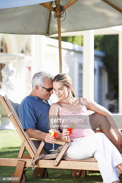 affectionate couple sit under a parasol on a sun lounger holding cocktail glasses - may december romance stock photos and pictures