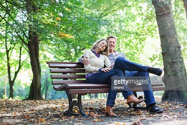 Affectionate  couple sitting on a park bench