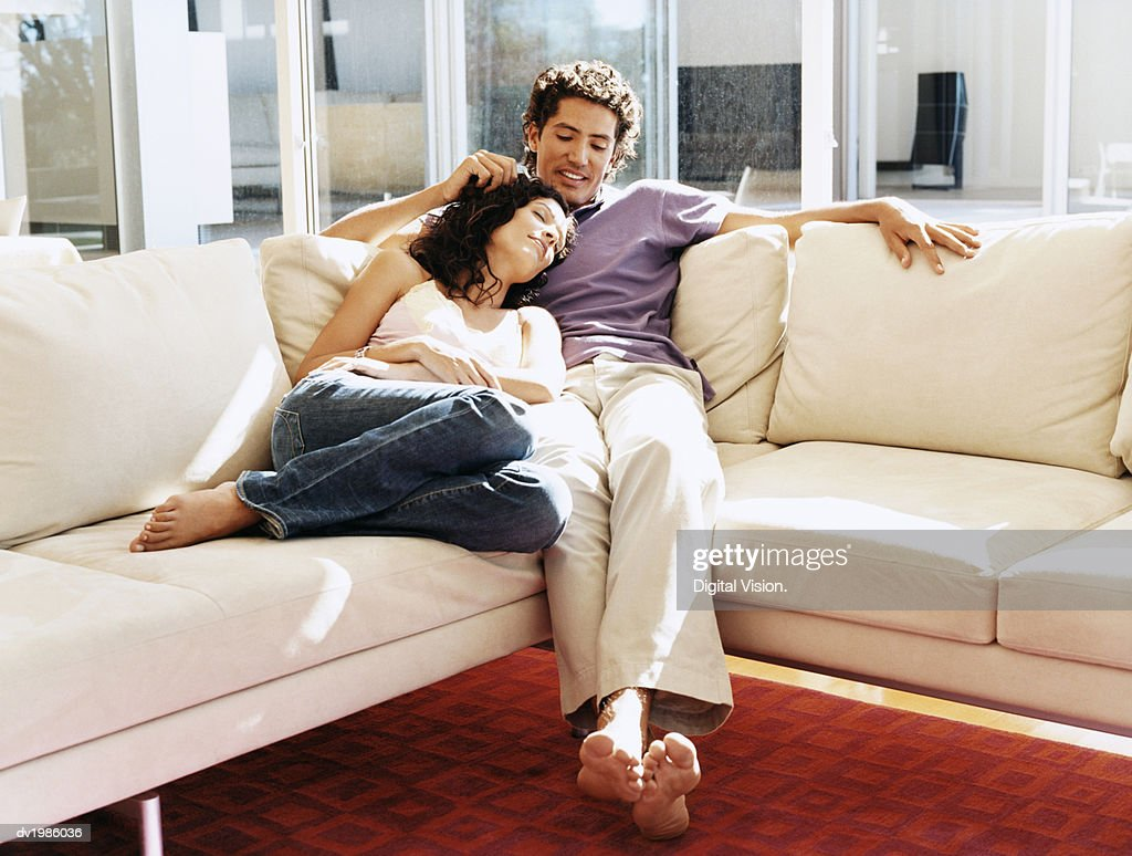 Affectionate Couple Sitting on a Sofa at Home : Stock Photo