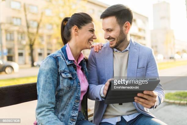 Affectueux couple assis sur un banc et à l'aide de tablette numérique