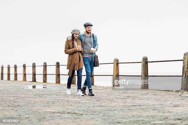 Affectionate couple walking on footpath at seaside