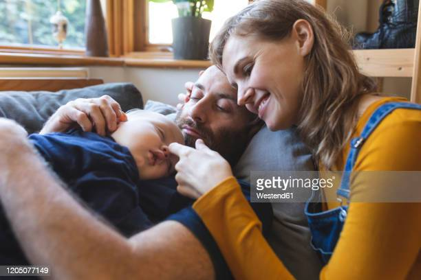 affectionate family on the sofa with sleeping little son - baby stock pictures, royalty-free photos & images