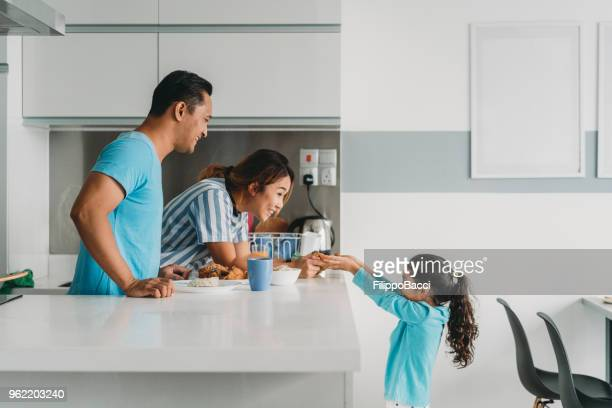 affectionate family preparing lunch at home - malaysian culture stock pictures, royalty-free photos & images