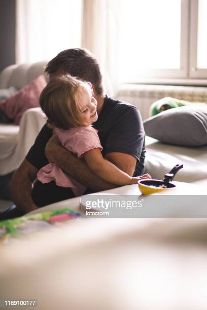 affectionate father cuddling his toddler daughter while they are playing with toys together - padre single foto e immagini stock