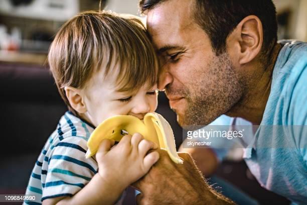 padre afectuoso alimentar a su niño pequeño con plátano. - banana fotografías e imágenes de stock