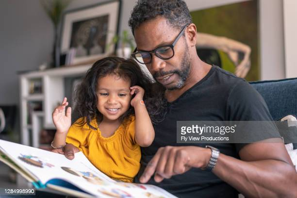 affectionate father reading book with adorable mixed race daughter - book stock pictures, royalty-free photos & images