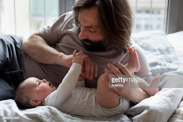 Affectionate father with baby girl in bedroom