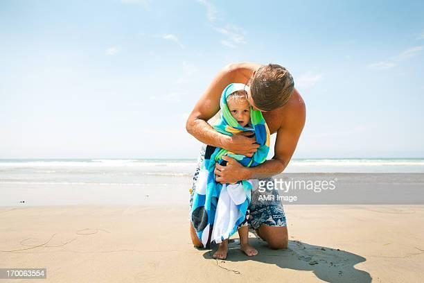 Zärtlich Vater seinen Sohn wrapps in ein Handtuch