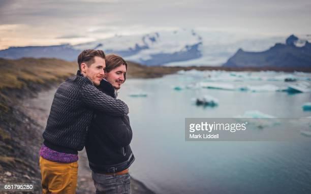affectionate gay couple hugging at jokulsarlon glacier lagoon, iceland - beautiful gay men photos et images de collection