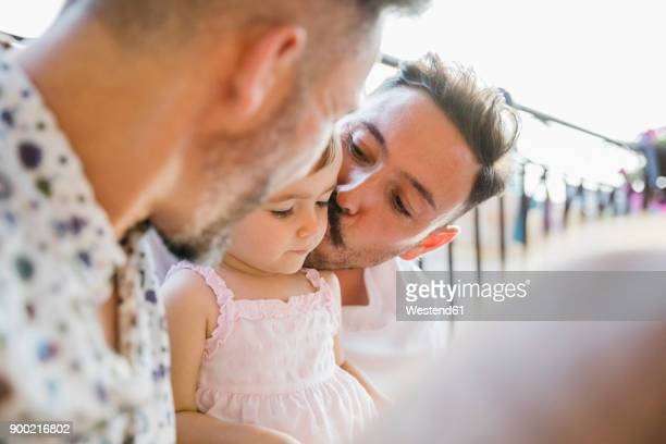 Affectionate gay couple with daughter on balcony