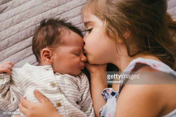 affectionate girl lying on blanket cuddling with her baby brother - geschwister stock-fotos und bilder