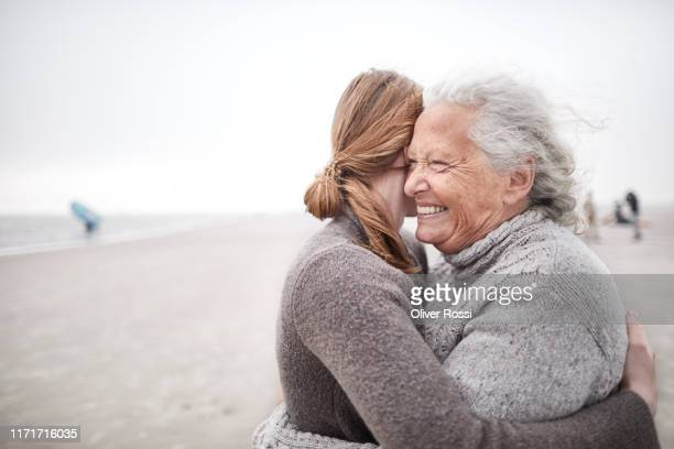 affectionate grandmother and granddaughter hugging on the beach - cuidado fotografías e imágenes de stock