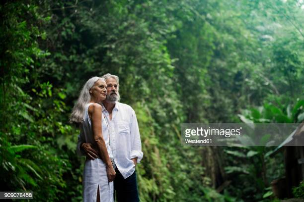 Affectionate handsome senior couple in tropical jungle
