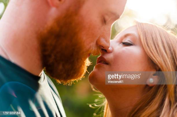 affectionate heterosexual couple kissing in park - kissing stock pictures, royalty-free photos & images