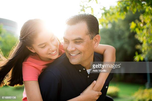 Affectionate latin father and teen daughter smiling