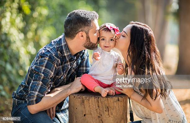 Affectionate latin parents kissing baby daughter on cheeks