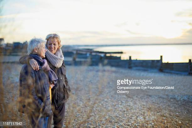 affectionate lesbian couple looking out to sea at sunset - sunday stock pictures, royalty-free photos & images
